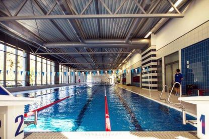 Eine große Schwimmhalle mit getrennten Bahnen und einer Aufsicht