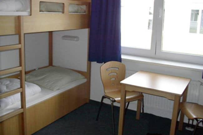 Große Zimmer mit mehreren Betten und einem Gruppentisch