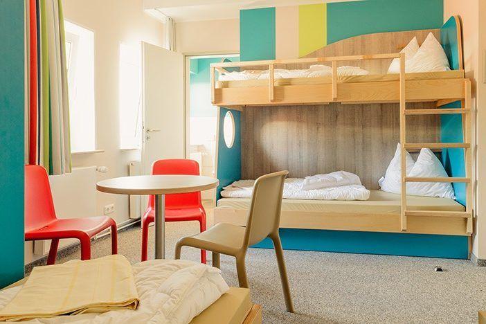 Die Zimmer bestehen aus mehreren Betten und in der Mitte steht noch ein kleiner Tisch mit Stühlen