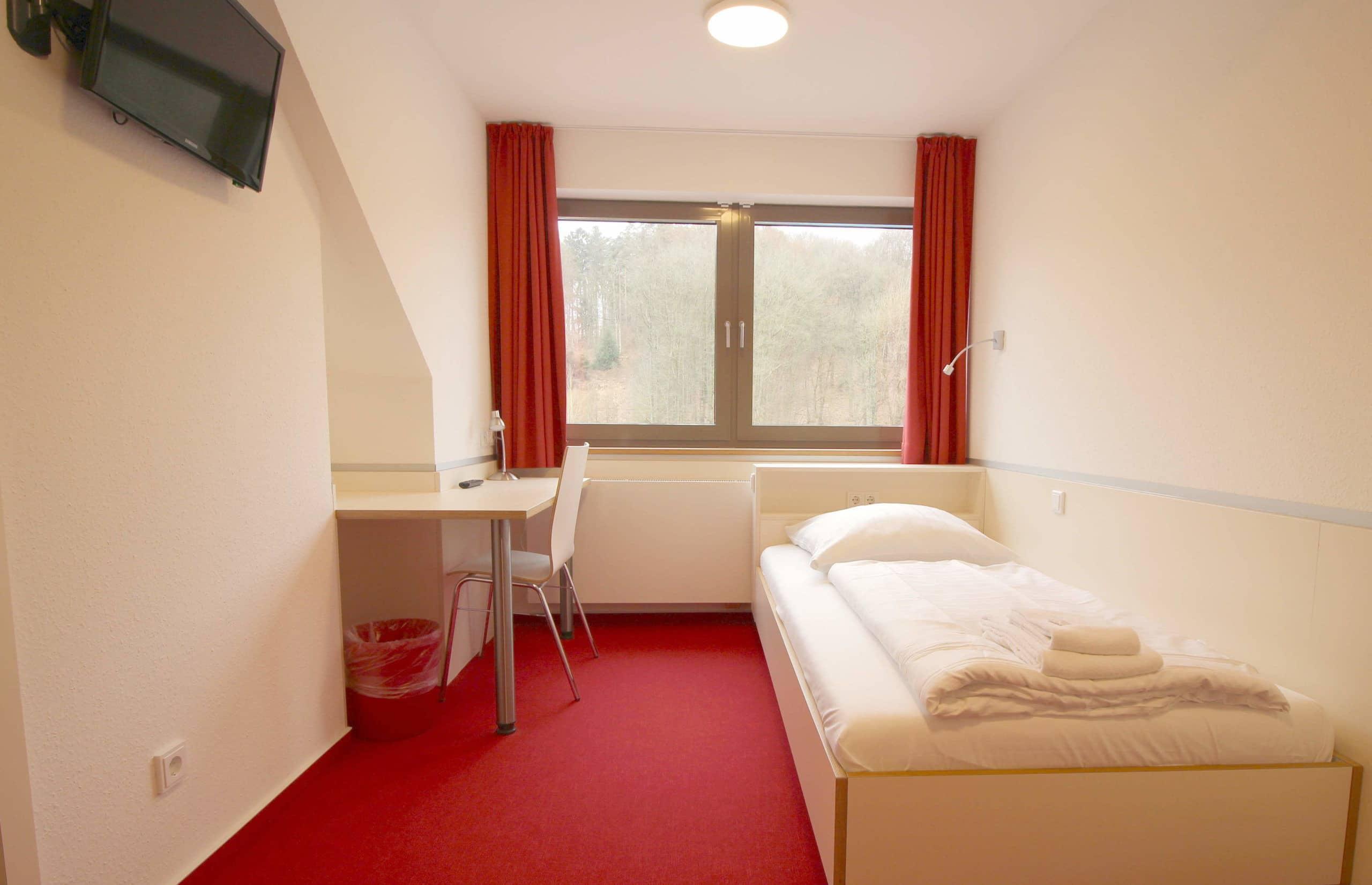 Komfortables Einzelzimmer mit eigenem Fernseher und Schreibtisch